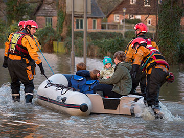 Family being rescued in dinghy from flood