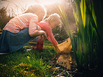 Two girls pond dipping