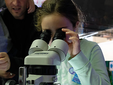 Girl looking into microscope